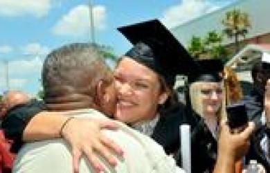 Source: Orlando Sentinel – graduate hugging man